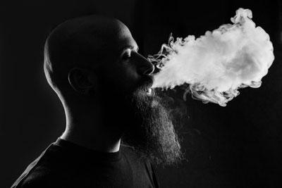Vaper exhaling a cloud of vapour with e cigarette