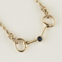 "A 14k gold bit with buckles necklace with a 3.5mm center sapphire of .19 carat. 16"" in length. Another classic piece!"