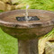Solar powered water fountain has a bubbler head to spray water up for a splashing water fountain sound effect.