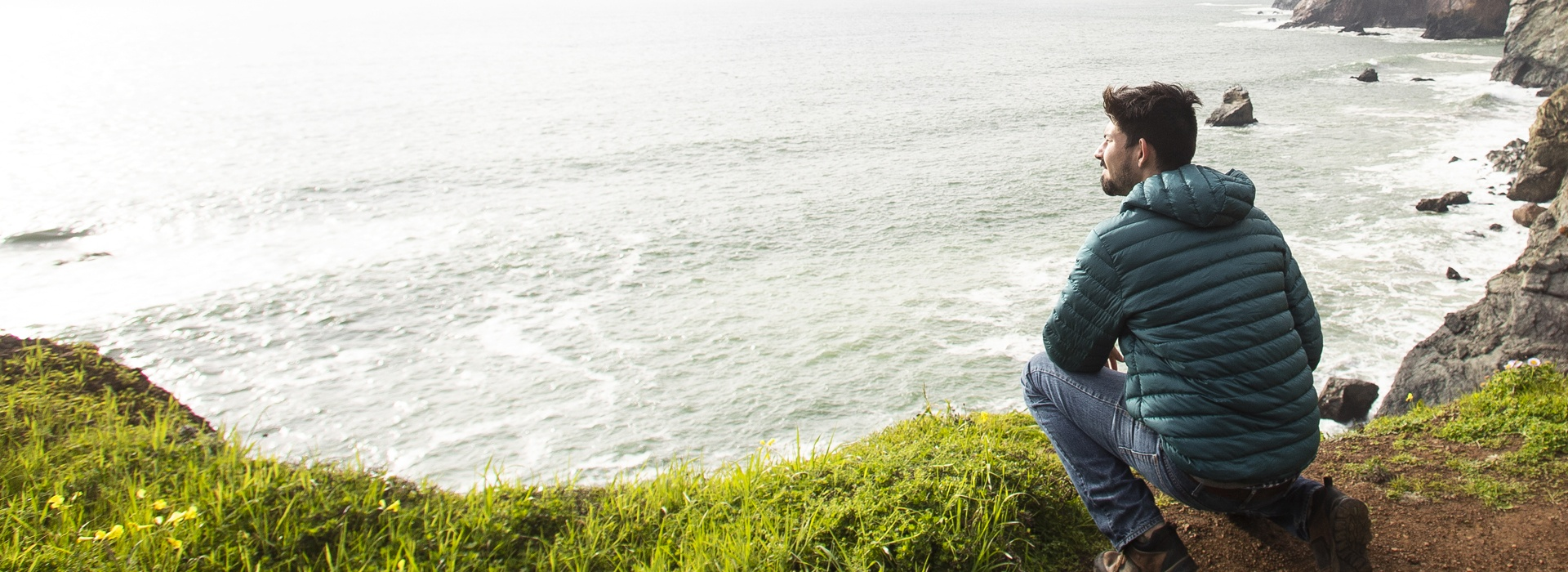 Man kneeling beside a cliff overlooking the ocean