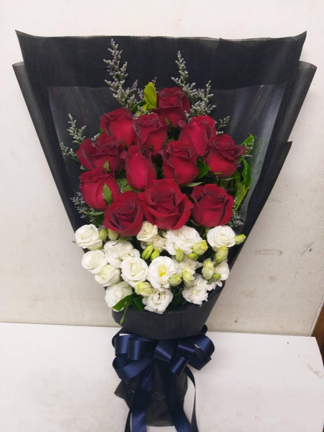ช่อดอกกุหลาบสีแดงและสีขาวห่อด้วยกระดาษสีดำ ดูหรูหราและลึกลับไปในตัว