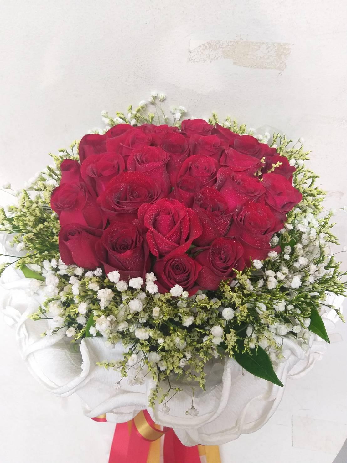 ช่อดอกกุหลาบทรงกลมประกอบด้วยกุหลาบแดงที่สื่อแทนความรักอันโรแมนติก