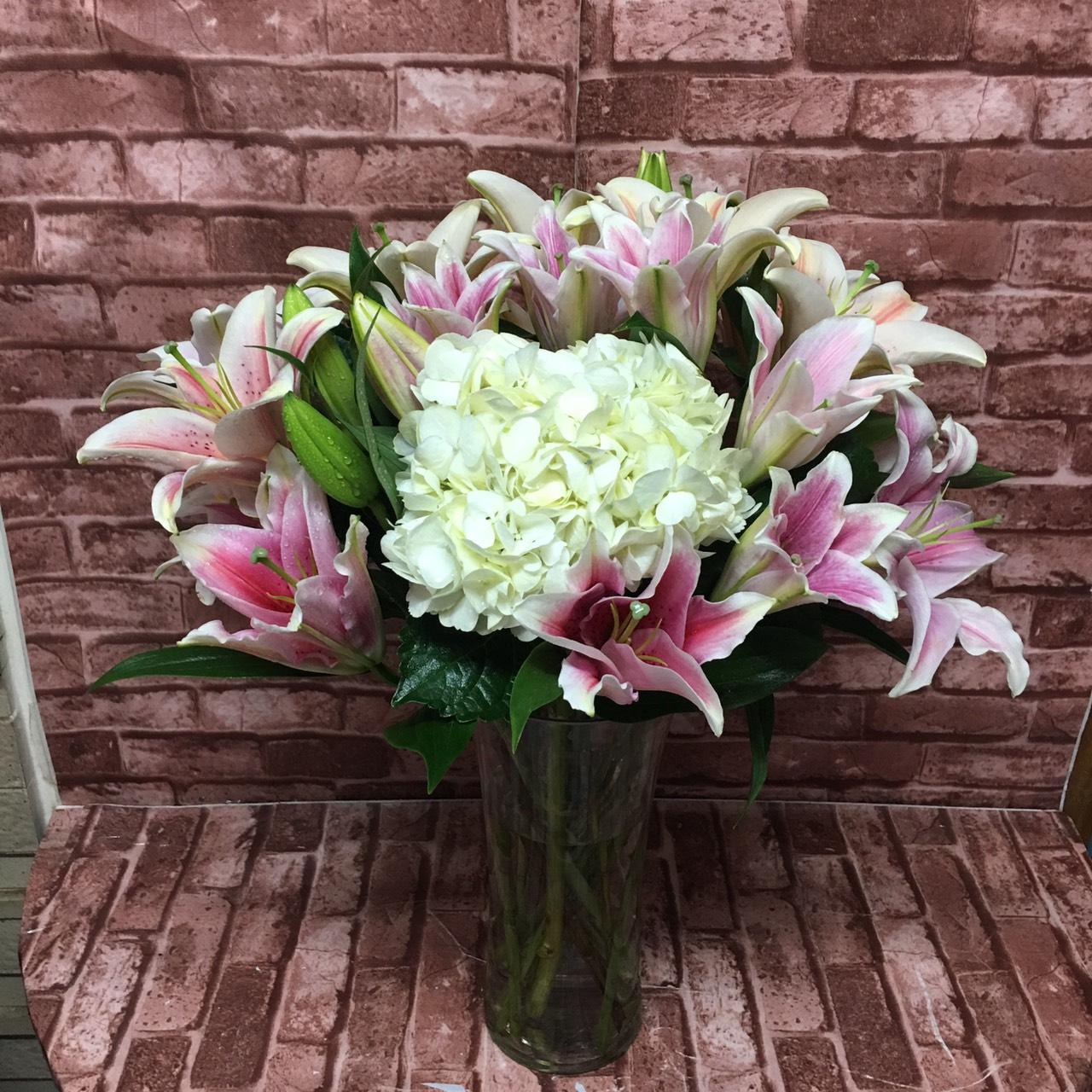 ดอกลิลลี่สีชมพูหวาน นำมาจัดใส่แจกันดอกไม้อย่างประณีตเอาใจใส่