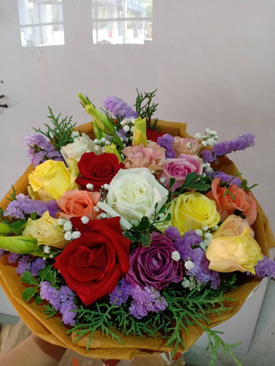 ช่อดอกไม้ทรงกลมประกอบด้วยดอกไม้หลากสีสันนานาพันธุ์ จัดตกแต่งอย่างสวยงาม