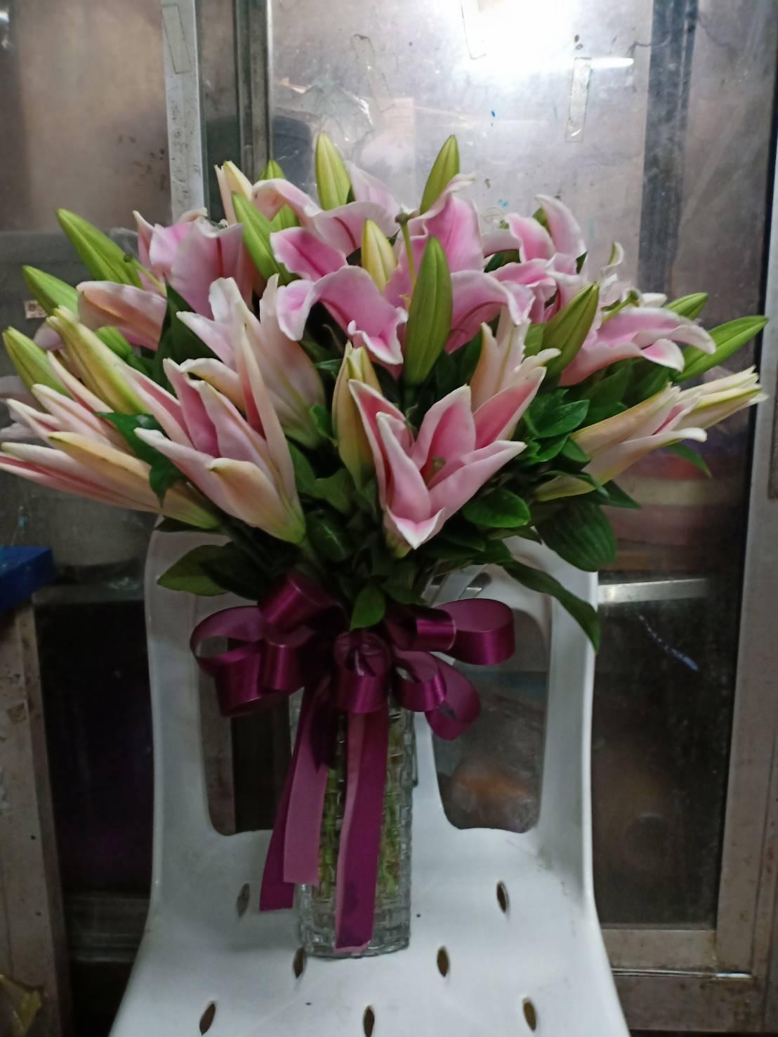 ดอกลิลลี่สีชมพูอ่อน เรียงใส่แจกันดอกไม้จนได้เป็นงานศิลป์ชั้นเยี่ยม