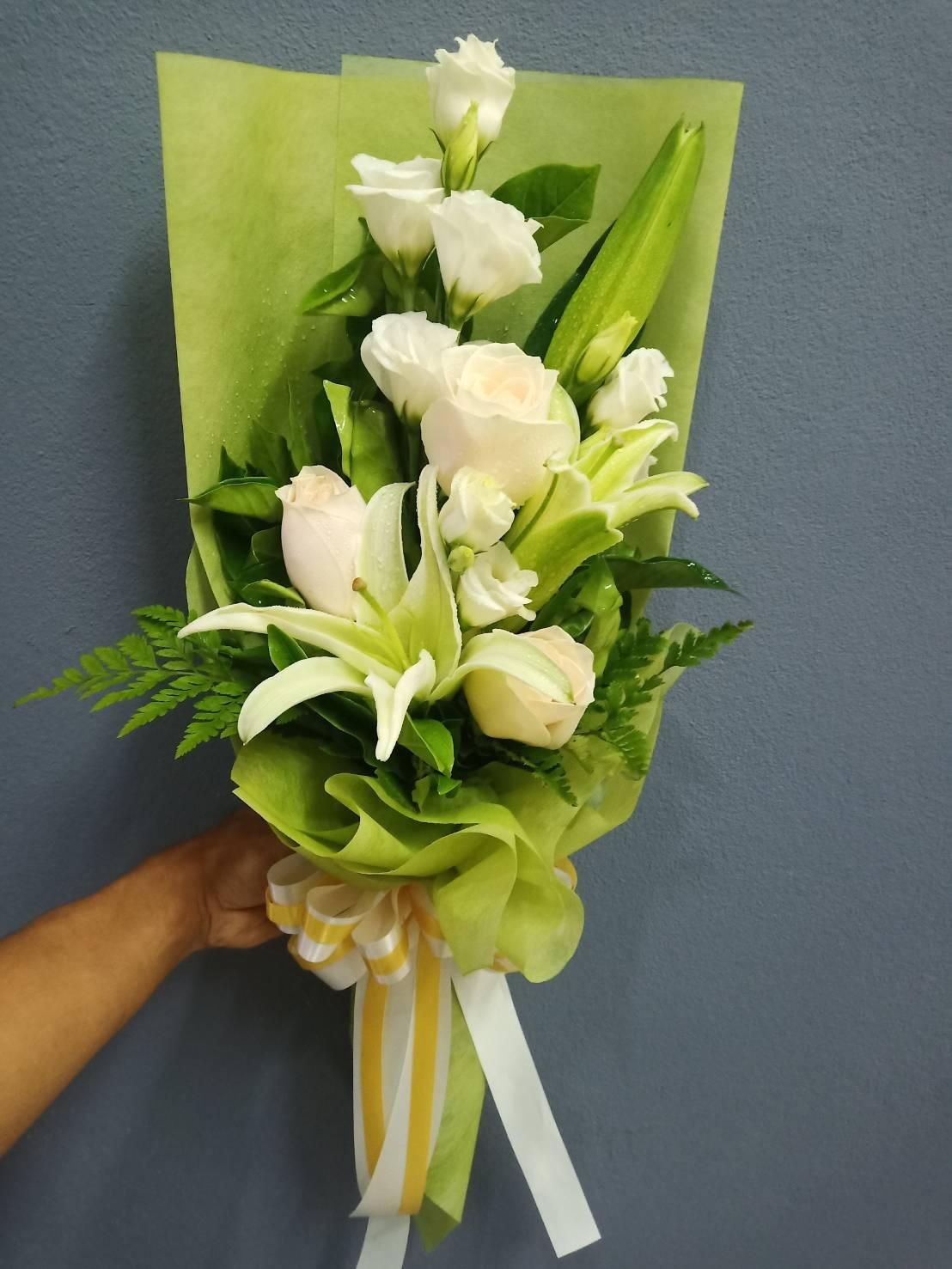 ช่อดอกกุหลาบสีขาวที่สื่อถึงความรักอันบริสุทธิ์ห่อด้วยกระดาษสีเขียวอย่างสวยงาม