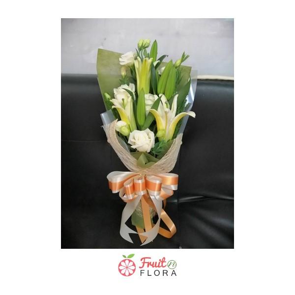 ช่อดอกไม้ทรงสูงจัดแต่งด้วยดอกไม้สีขาวอย่างดอกกุหลาบและดอกลิลลี่ ห่อด้วยกระดาษห่อหลายชั้นอย่างสวยงาม