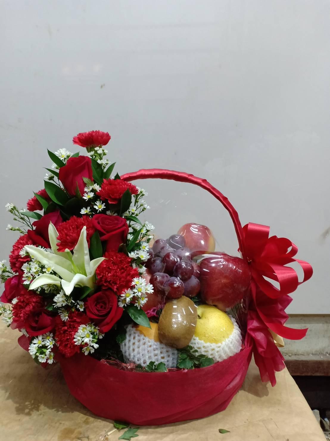 กระเช้าผลไม้ประกอบไปด้วยผลไม้สดตามฤดูกาล โดดเด่นสะดุดตาด้วยดอกกุหลาบและดอกเบญจมาศสีแดง