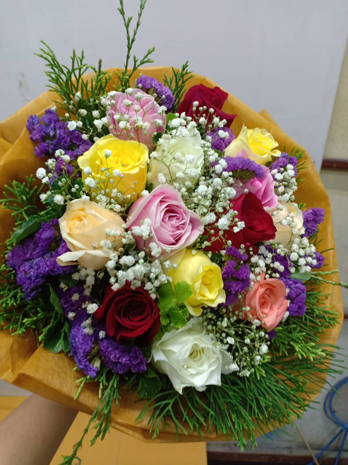 ดอกกุหลาบคละสีแซมด้วยดอกสแตติสและดอกยิปโซถูกจัดแต่งรวมกันเป็นช่ออย่างสวยงาม