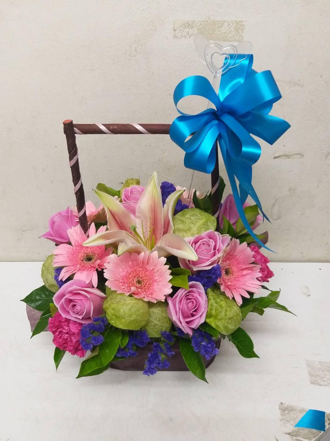 ดอกไม้สดโทนสีชมพู-ม่วงหลากชนิดถูกจัดตกแต่งไว้ในกระเช้าอย่างสวยงาม