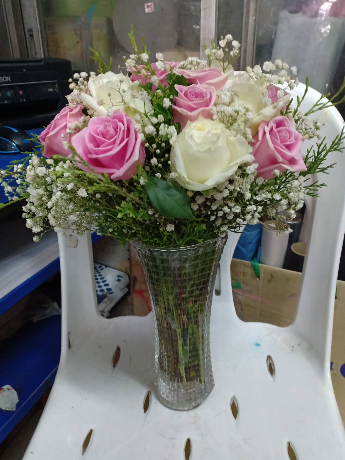 ดอกกุหลาบสีขาวและสีชมพู แซมด้วยดอกยิปโซปักลงในแจกัแก้วอย่างสวยงาม