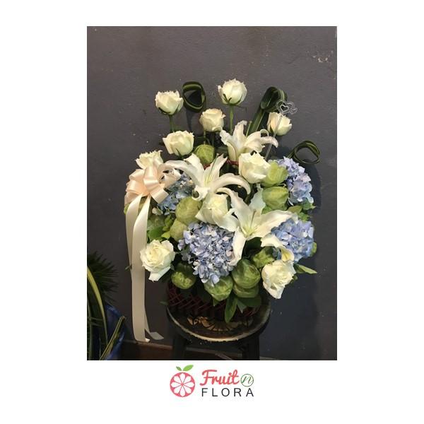 กระเช้าดอกไม้สวย ๆ จัดตกแต่งด้วยดอกกุหลาบ ลิลลี่ และไฮเดรนเยีย โทนสีขาว-เขียว-ฟ้า สวยงาม