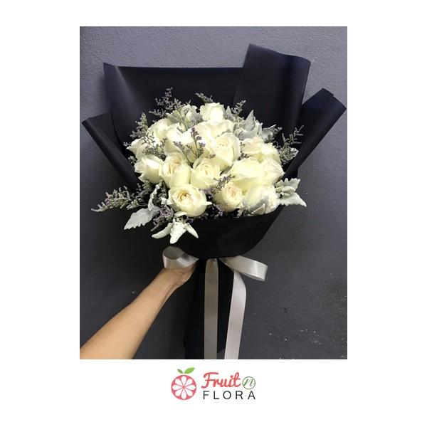 ช่อดอกกุหลาบสีขาวแซมด้วยดอกสุ่ยและดอกยิปโซอย่างสวยงาม ห่อด้วยกระดาษห่อสีน้ำเงิน