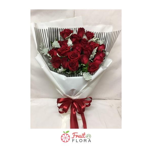 ช่อดอกกุหลาบแดง ตกแต่งอย่างสวยงามในกระดาษห่อสีขาวลายทางสีดำ