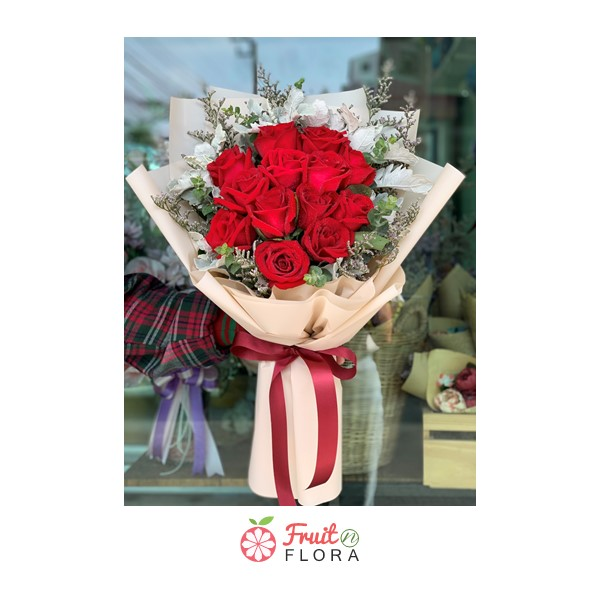 ช่อดอกกุหลาบแดงห่อด้วยกระดาษสีครีม แซมด้วยดอกไม้ประดับอย่างสวยงาม