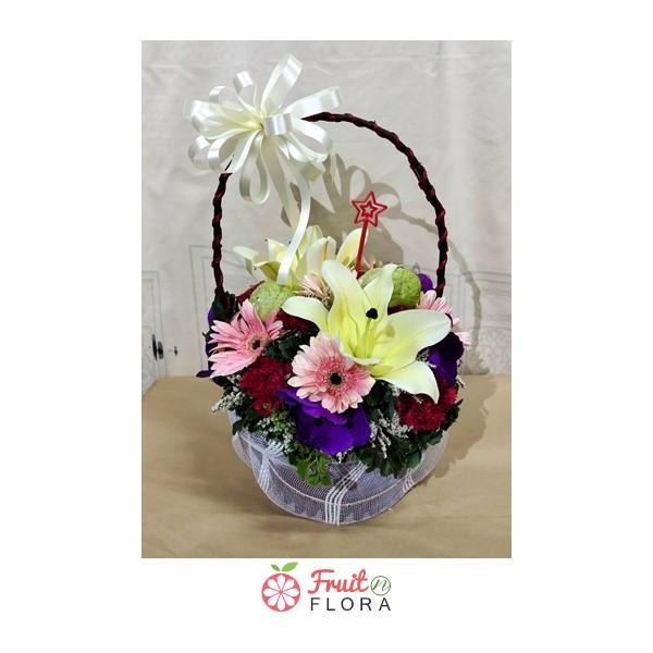 กระเช้าดอกไม้บรรจุดอกไม้สวย ๆ หลากหลายชนิด ผูกริบบิ้นสีขาว
