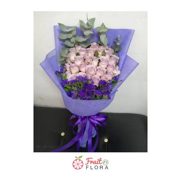 ช่อดอกกุหลาบโทนสีชมพูพาสเทล แซมดอกสแตติส ห่อด้วยกระดาษห่อสีม่วงอย่างสวยงาม