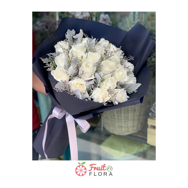 ช่อดอกกุหลาบขาวสวย ๆ ห่อด้วยกระดาษสีน้ำเงินสุดหรู สื่อถึงความรักแท้อันบริสุทธิ์