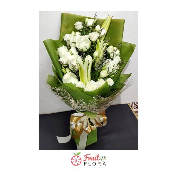 ช่อดอกกุหลาบสีขาวห่อด้วยกระดาษสีเขียวอย่างสวยงาม