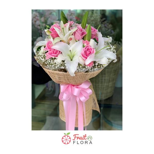 ช่อดอกกุหลาบสีชมพูแซมด้วยดอกลิลลี่สีขาว ห่อด้วยกระดาษกระสอบอย่างสวยงาม