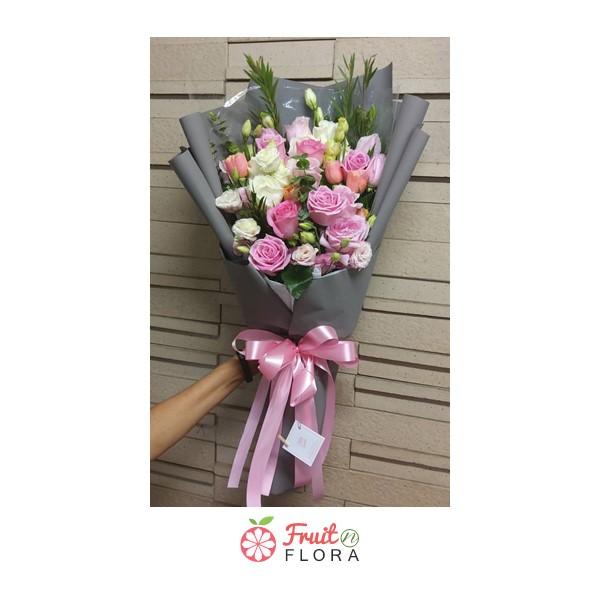 ช่อดอกกุหลาบสีขาวและสีชมพูจัดรวมกันในห่อกระดาษสีเทา สื่อความรักอันบริสุทธิ์และอ่อนโยน