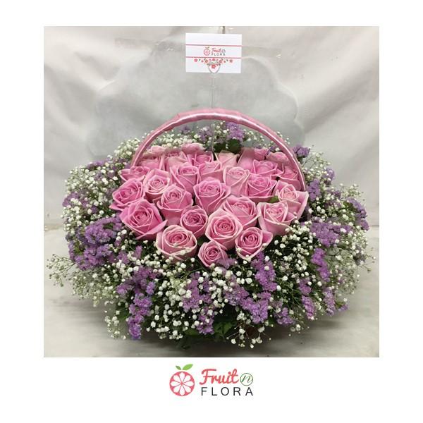 กระเช้าดอกไม้โทนสีชมพู จัดแต่งด้วยดอกกุหลาบ แซมดอกยิปโซและดอกสแตติสอย่างสวยงาม