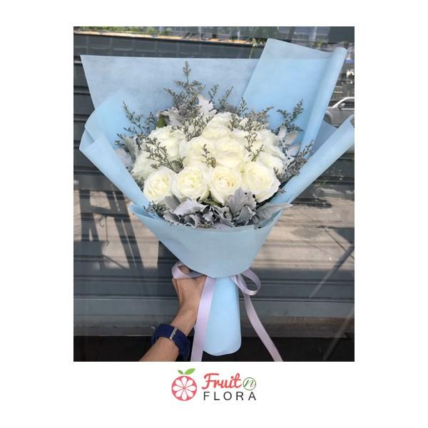 ช่อดอกกุหลาบสีขาวแซมด้วยดอกสุ่ยและดอกยิปโซห่อด้วยกระดาษสีฟ้าอย่างสวยงาม