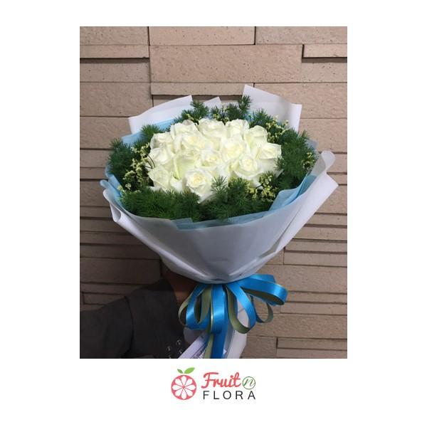 ช่อดอกไม้ทรงกลมห่อด้วยกระดาษสีขาวและสีฟ้า จัดแต่งด้วยกุหลาบสีขาวล้อมรอบด้วยดอกสุ่ยอย่างสวยงาม