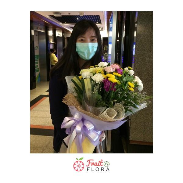 ผู้หญิงน่ารักถือช่อดอกไม้ไซส์มินิ ดีไซน์เก๋ ๆ ที่ได้รับจากหนุ่มคนรู้ใจ