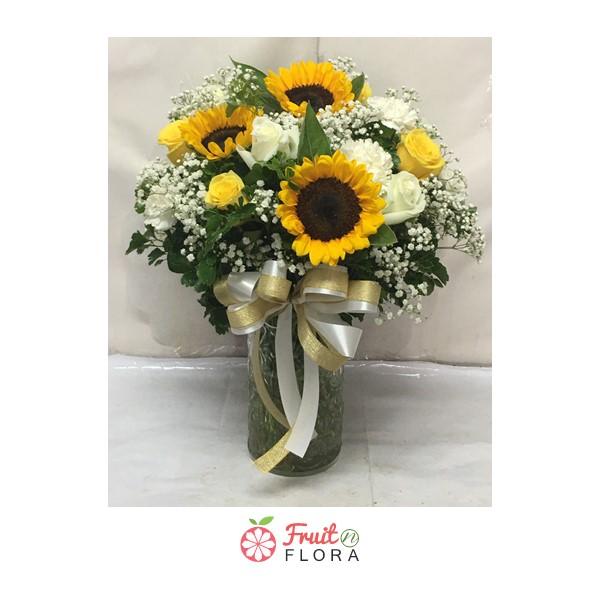 ดอกทานตะวันกับดอกกุหลาบขาวแซมด้วยดอกสุ่ย จัดอยู่ในขวดโหลแก้ว ให้ความรู้สึกสวยงามและอบอุ่นใจจริง ๆ ค่ะ