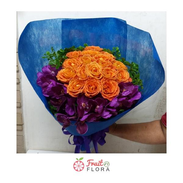 ช่อดอกกุหลาบสีส้มแซมด้วยดอกกล้วยไม้ห่อด้วยกระดาษห่อสีน้ำเงิน