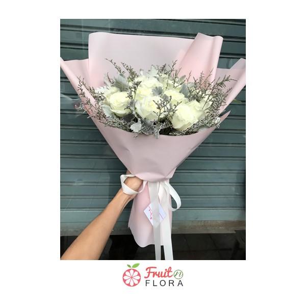 ช่อดอกกุหลาบขาวแซมด้วยดอกยิปโซห่อด้วยกระดาษสีชมพูอย่างสวยงาม