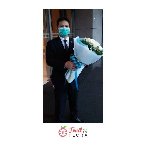 ช่อดอกกุหลาบสีขาวห่อด้วยกระดาษสีฟ้า ให้ความรู้สึกอบอุ่นและเย็นสบาย