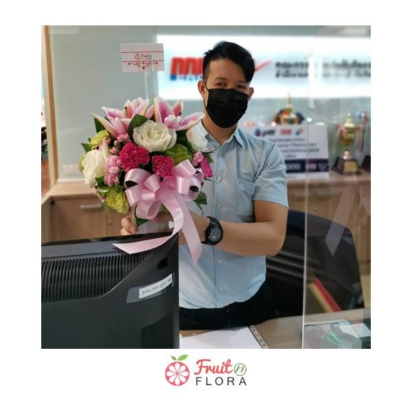 ผู้ชายใส่หน้ากากผ้าสวมเสื้อเชิ้ตยืนถือแจกันดอกไม้สวย ๆ โทนสีหวาน ๆ