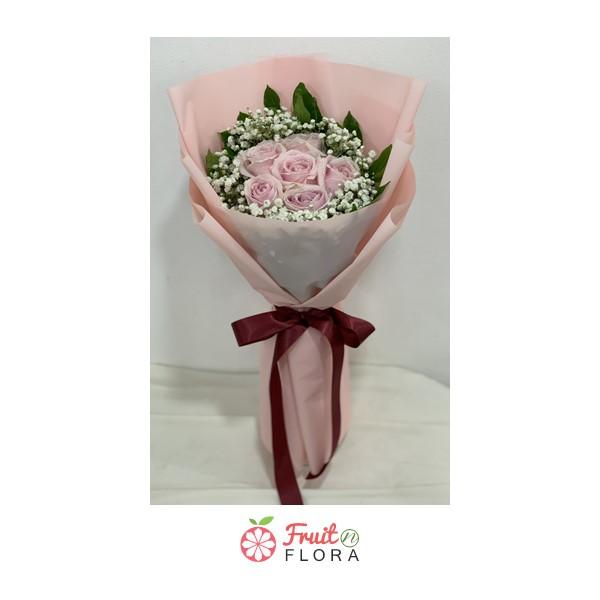 ดอกกุหลาบสีชมพูแซมด้วยดอกสุ่ย ถูกจัดเป็นช่อรวมกันในกระดาษห่อสีครีม ผูกด้วยริบบิ้นสีเลือดหมู