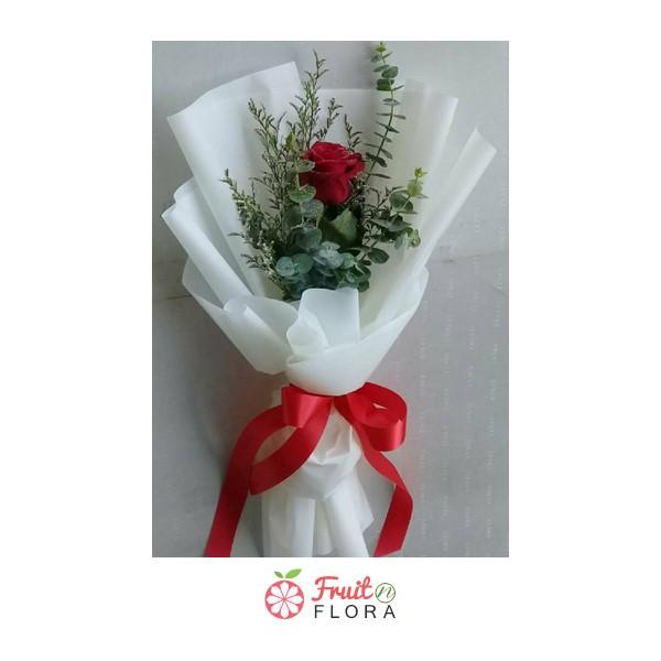ดอกกุหลาบสีแดงหนึ่งดอกแซมด้วยใบไม้สีเขียว ห่อด้วยกระดาษห่อสีขาว ดูสวยงามแบบคลาสสิก
