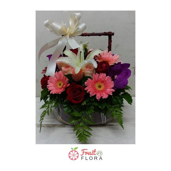 กระเช้าดอกไม้ขนาดกะทัดรัด ถือสบายมือ ตกแต่งด้วยดอกไม้หลากสีสันนานาพันธุ์ ผูกริบบิ้นสีขาวอย่างสวยงาม