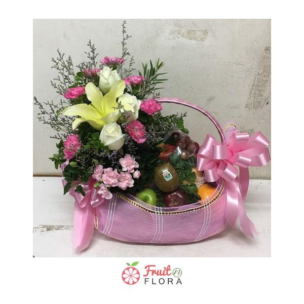 กระเช้าผลไม้ใบสีชมพูขนาดกะทัดรัด บรรจุผลไม้สดตามฤดูกาล ประดับด้วยดอกไม้สดอย่างสวยงาม