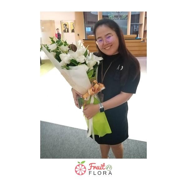 ช่อดอกไม้สวย ๆ ที่ประกอบด้วยช่อดอกกุหลาบสีขาวและลิลลี่สีขาว ห่อด้วยกระดาษห่อสีเขียวอย่างสวยงาม