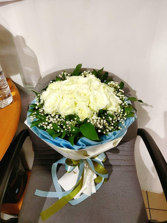 ช่อดอกกุหลาบสีขาวนวลแซมด้วยดอกสุ่ย ห่อด้วยกระดาษห่อสีขาว-ฟ้าอย่างสวยงาม