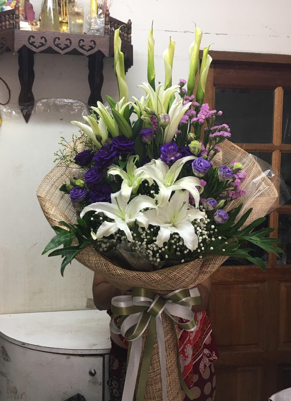 ช่อดอกไม้ทรงสูง จัดแต่งด้วยดอกลิลลี่และดอกสแตติส มองแล้วสบายตา ได้รับแล้วอุ่นใจ