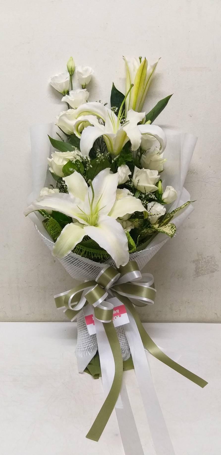 ดอกกุหลาบและดอกลิลลี่สีขาว ถูกจัดรวมกันเป็นช่อเดียวอย่างสวยงามและมีเสน่ห์