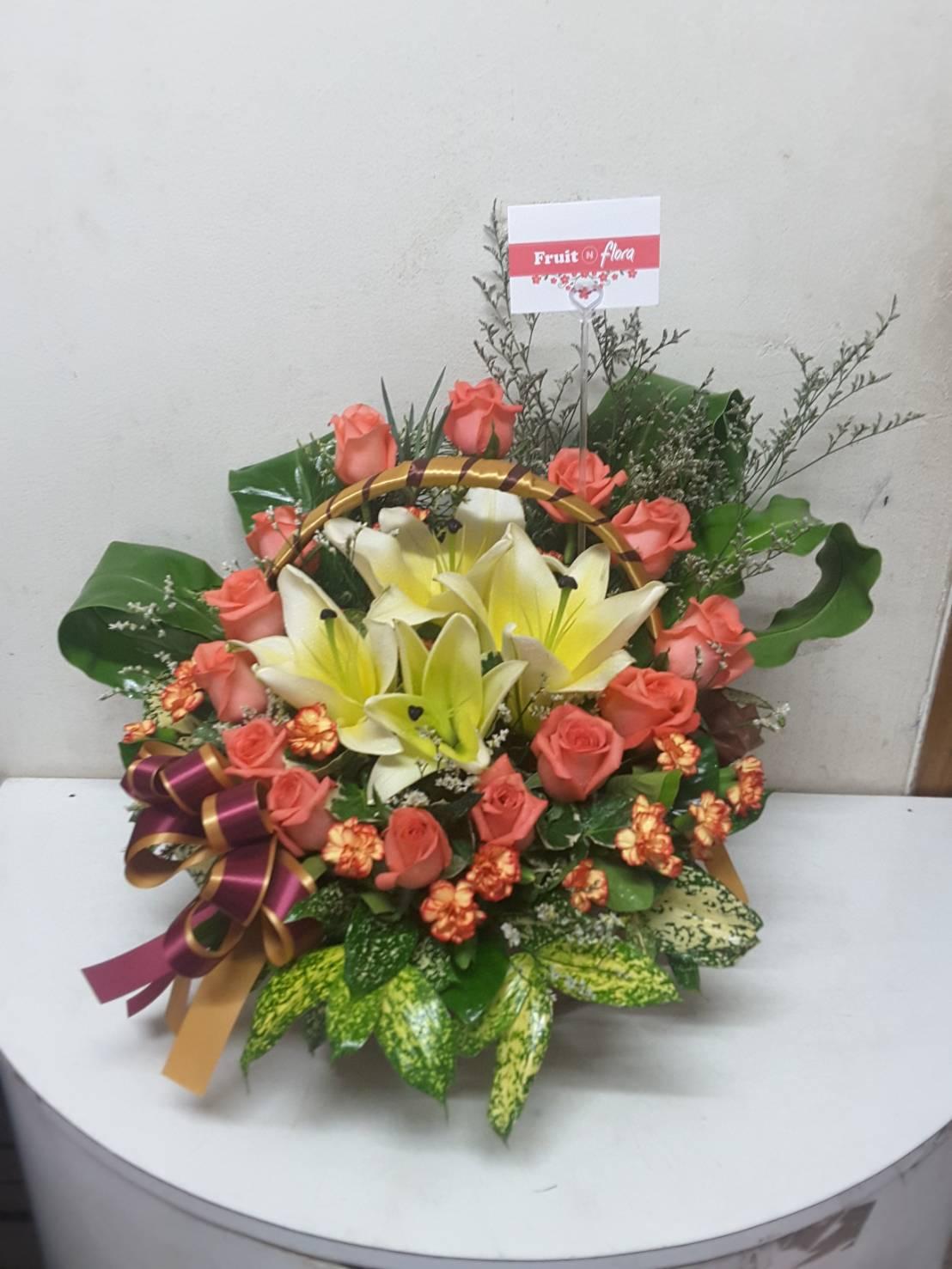 กระเช้าดอกไม้สวยๆ สดใสๆ ตกแต่งด้วยดอกกุหลาบ ลิลลี่ และคาร์เนชั่น โดดเด่นสะดุดตา