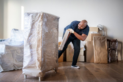 man wrapping furniture in plastic