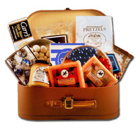 Travel themed gift basket arrangement with chocolates, sweet and salty snacks, dried fruit, caramels, and cookies