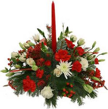 Candle centerpiece with fresh evergreens and traditional red and white flowers.