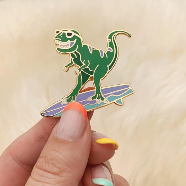 AC00149-GLD-OS Surfing Dinosaur Enamel Pin - T-Rex Enamel Lapel Pin -Surfing Enamel Pin - Cute Dinosaur Pin - Surfing Gifts for Women - Surfer - Wildflower + Co - VSCO