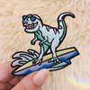 TR00476-MLT-OS - Surfing Dinosaur Patch, Small - Patches, Patch, Iron On, Iron On Patches, Patches for Jackets, Embroidered Patches, Embroidery, Embroidered, Cute Patch, Adorable Patch, Dinosaur Patch, Dino Patch, Surfing Dinosaur