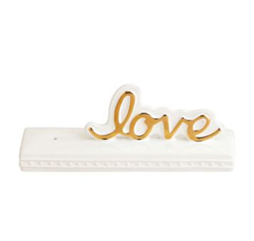 "This new Nora Fleming ""Love"" sign has so many possibilities! It will make an adorable accessory for all over your home!  Imagine one piece that changes for every holiday, event or season. All you have to do is remove one mini, add another and presto a whole new look!     Dimensions: 10"" x 3"" X 4""      Compatible with Nora Fleming mini ornaments (sold separately)     How it works:  Step 1: Dab the hole of your sign with water Step 2: Insert the decorative mini of your choice Step 3: Pull the stem down from the bottom so that the mini sits flush on the rim"