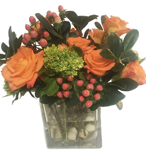 Fresh floral arrangement with coral roses, mini green hydrangeas, spray roses and hypericum.